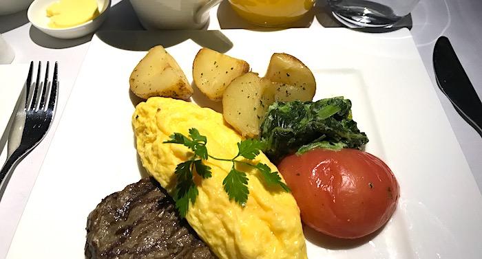 機内のオムレツとステーキの食事