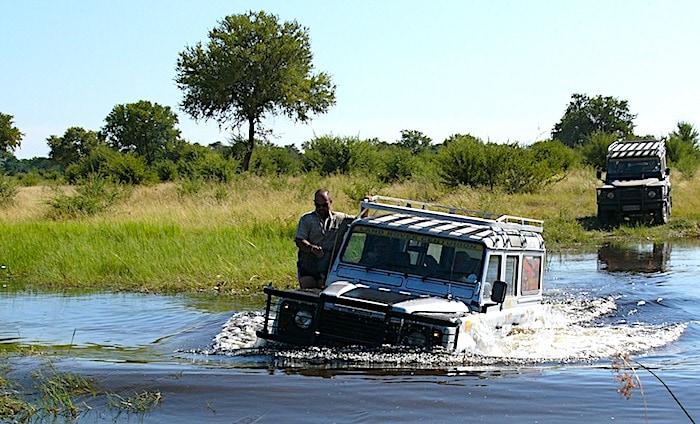 湿地の沼を走るジープ