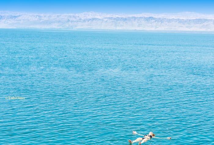 死海に浮かぶ人の画像